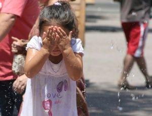 Una pequeña santiaguina mojándose la cara para refrescarse [Créditos: Jorge Peralta, Publimetro]